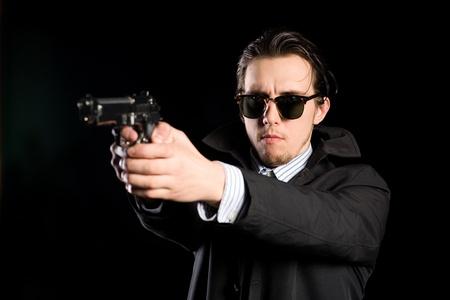 hombre disparando: El hombre disparando una pistola en el negro. Foto de archivo