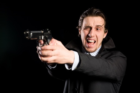 Aggressive man shooting a gun photo