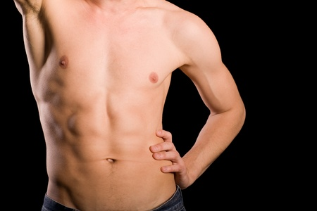 Trained young man naked torso on a black background. photo