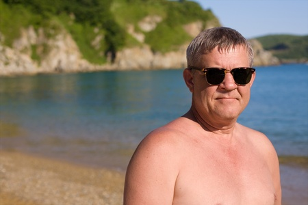 Handsome middle aged man sunbathes on the beach photo