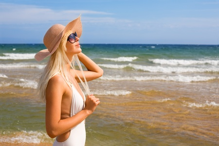 Beautiful girl in the hat on the beach photo