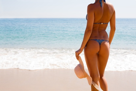 Slim tanned figure of a girl against the sea photo
