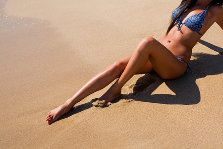 tanned body: Tanned girl in bikini is sitting on the sand by the sea. Stock Photo