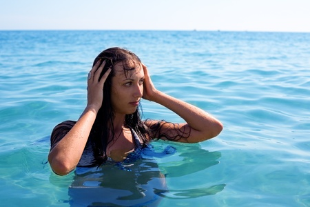 beautiful young brunette swims in the sea photo