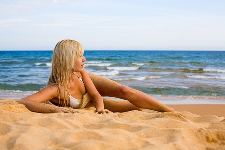 Beautiful blonde girl lying on the beach photo