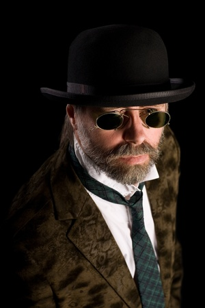 Stilish man in vintage sunglasses pince nez and bowler hat photo