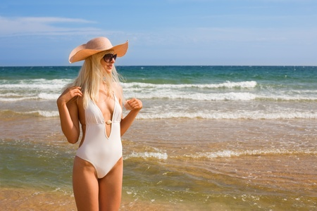 Attractive young woman in a hat at the beach photo