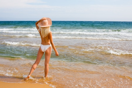 Slim blonde girl wearing a hat at the beach photo