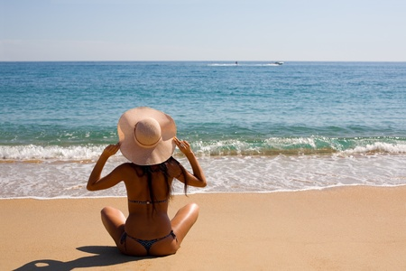 Beautiful young woman in a hat at the beach photo