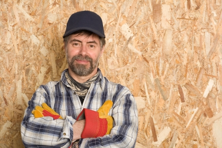Smiling carpenter on a background sheet of plywood photo