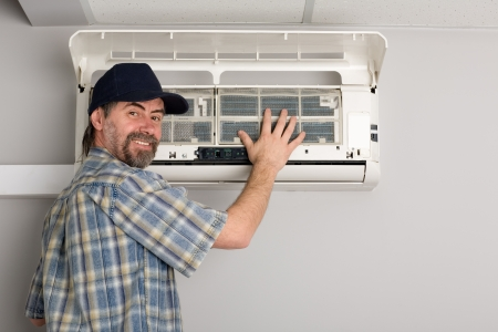 air conditioning: Repairer conducts adjustment of the indoor unit air conditioner.  Stock Photo