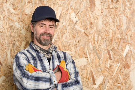 carpenter in a cap on the background sheet of plywood. Stock Photo - 13701873