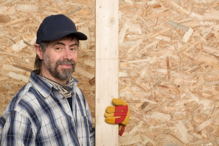 Carpenter holds a plaque on a background sheet of plywood. Stock Photo 7873163dd219