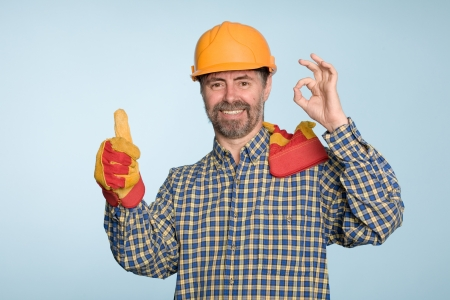Happy smiling successful builder with thumbs up gesture photo