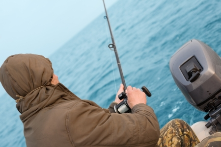 Fisherman catches a salmon trolling in the sea. Stock Photo - 13718815