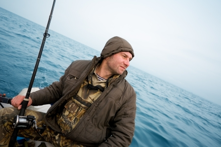 Angler fisherman catches a salmon trolling in the sea. Stock Photo - 13718814
