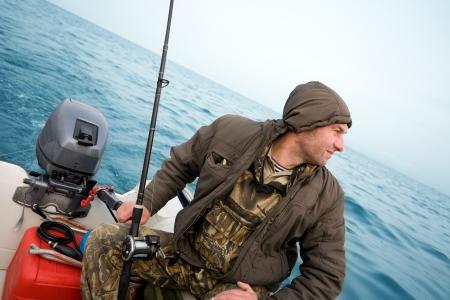 Fisherman fishing a salmon trolling in the sea. Stock Photo - 13718813