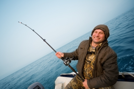 fisher: Fishing salmon. Fisher holds trolling rod. Focus on the right hand. Stock Photo