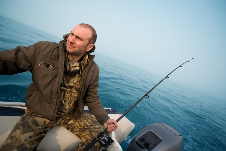 Fishing for salmon. Fisher holds a trolling rod. photo