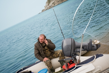 Fisherman was talking on his mobile phone after fishing in the sea. Фото со стока