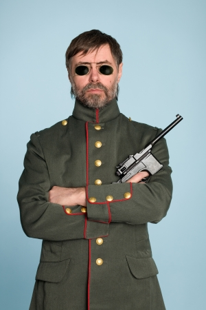Man in the uniform of a military officer with a gun. photo
