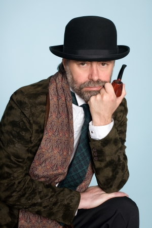 Portrait of middle-aged man in a hat and smoking a pipe. photo