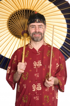 Caucasian in traditional Chinese shirt holding pipe  Umbrella is made of bamboo and paper  photo