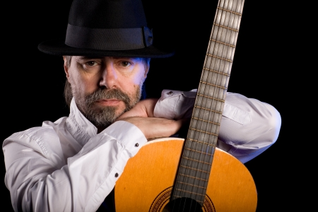 Portrait of popular musician with a guitar on black. photo