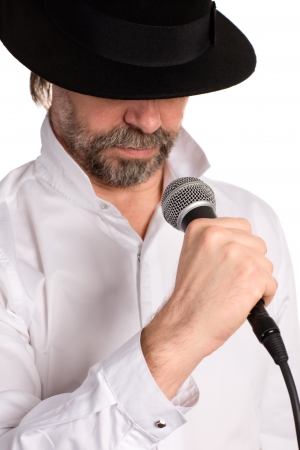 Portrait of a singer with microphone isolated on white. Focus on the microphone. photo
