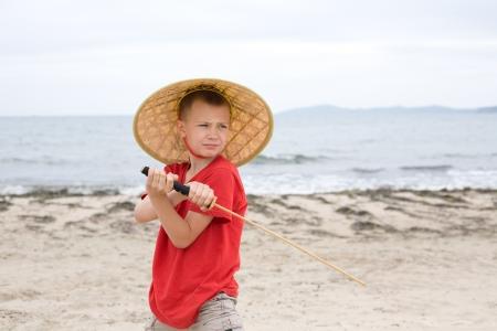 Boy plays with a samurai sword made of bamboo  photo