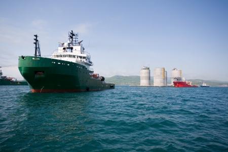 Ocean tugs towing base offshore oil drilling platform  Sea of Japan  Russian coast