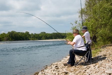 Joyful grandfather and grandson go fishing on the river.