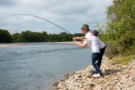 Gambling grandfather and grandson fishing.