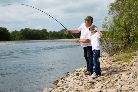Grandfather and grandson fishing on the river. photo