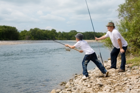 Gambling Grandfather and grandson fishing. photo
