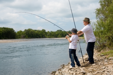 Happy grandfather and grandson fishing. photo