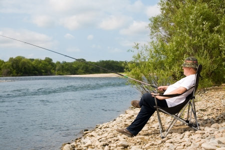 Visser vissen in de rivier. Man van middelbare leeftijd. Stockfoto