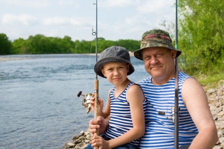 summer picnic: Portrait of grandfather and grandson fishing.