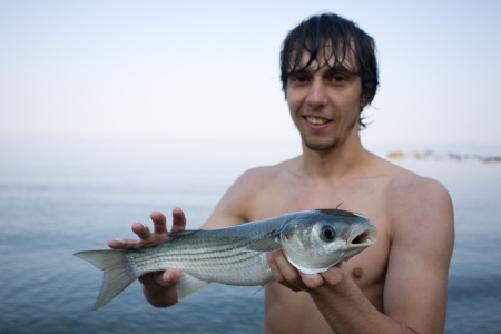 grey mullet: Fisher holds a freshly caught sea mullet  Sea of Japan