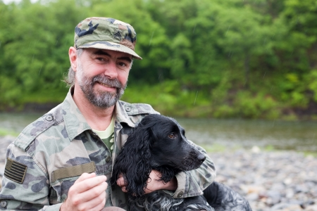 veterans: Middle aged man with a dog (Russian Hunting Spaniel), a uniformed sergeant US Army. At the river. Rain.  Stock Photo
