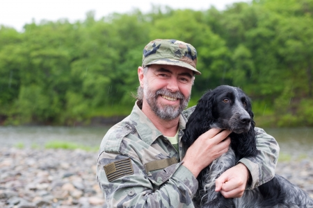 veteran: Middle aged man with a dog (Russian Hunting Spaniel), a uniformed sergeant US Army. At the river. Rain.