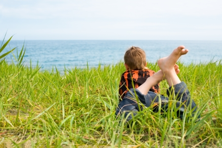 Happy boy lying on the grass and watching sea.