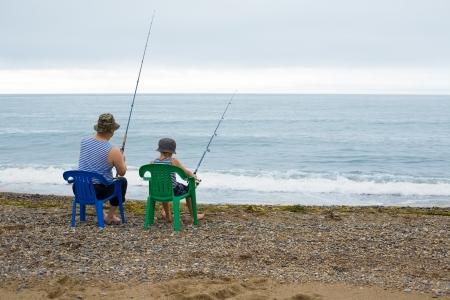할아버지와 손자의 바다에서 낚시를 이동합니다.