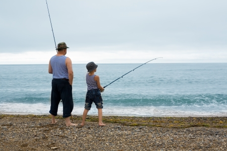 Grandfather and grandson fishing at the weekend at sea. Early in the morning. photo