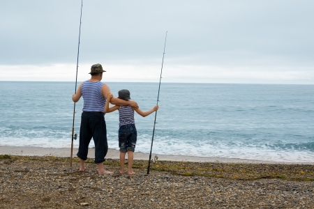 Grandfather and grandson fishing at the weekend at sea. photo