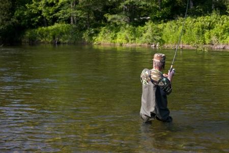 Fisherman pulls caught salmon. River. Stock Photo - 17718890