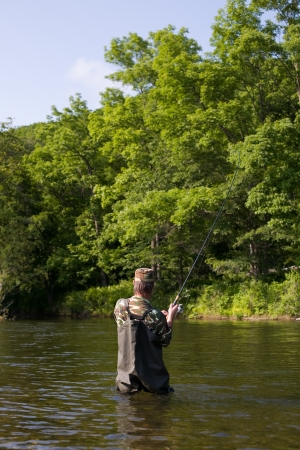 Fisherman pulls caught salmon in river. Stock Photo - 17718892