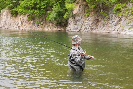 Fisherman catches of salmon in a mountain river  Stock Photo - 17750704
