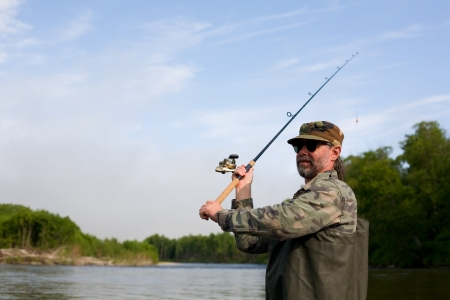 Fisherman makes casting tackle in the river  photo
