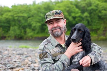 soldado: Hombre de mediana edad con un perro de caza Spaniel ruso en el río bajo la lluvia